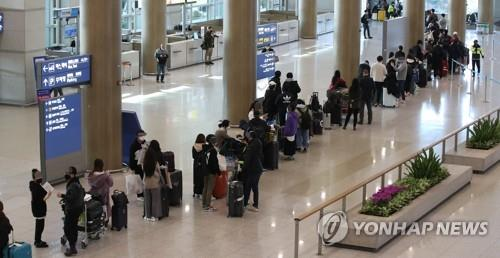 Passengers from London are in line in the arrival lobby of Incheon International Airport, west of Seoul, on March 23, 2020, to be bused to a nearby hotel, where they will undergo COVID-19 tests. (Yonhap)