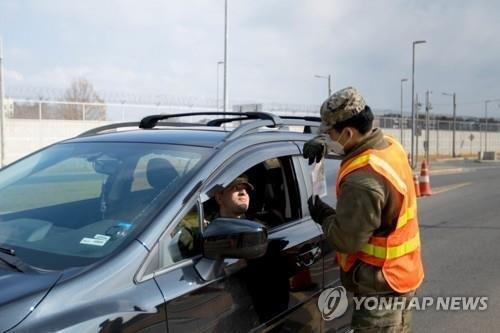 A military guard at U.S. Army Garrison Humphreys in Pyeongtaek, 70 kilometers south of Seoul, screens an entrant to the compound amid the novel coronavirus outbreak on April 5, 2020, in this photo provided by U.S. Forces Korea. (PHOTO NOT FOR SALE) (Yonhap)