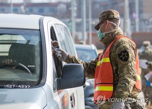 A military guard at U.S. Army Garrison Humphreys in Pyeongtaek, 70 kilometers south of Seoul, checks the temperature of a driver to screen entrants to the compound for the novel coronavirus on Feb. 28, 2020, in this photo provided by United States Forces Korea. (PHOTO NOT FOR SALE) (Yonhap)