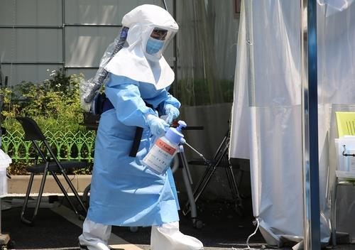 A heavily geared medical worker disinfects a COVID-19 screening station in Daejeon, central South Korea, on June 10, 2020. (Yonhap)
