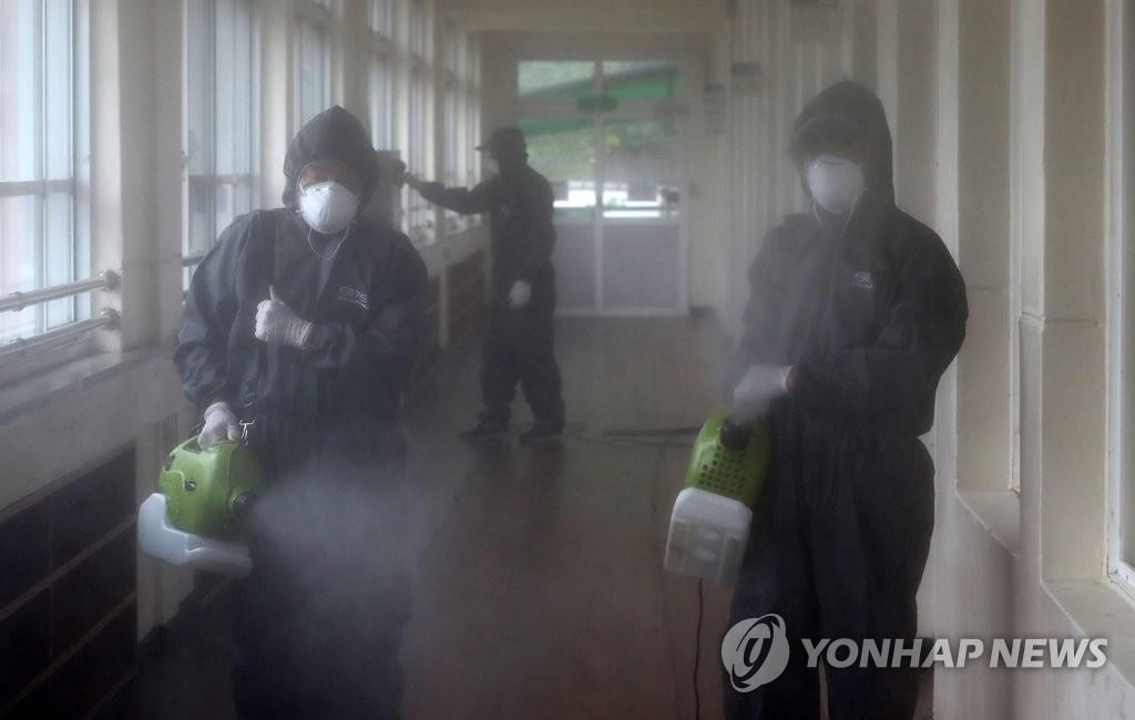 A disinfection crew sprays disinfectant at Cheondong Elementary School in Daejeon on June 30, 2020. (Yonhap)