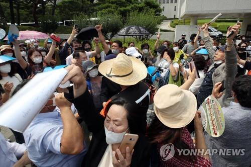 Lee Jae-myung's supporters cheer upon hearing the verdict in front of the Supreme Court in Seoul on July 16, 2020. (Yonhap)