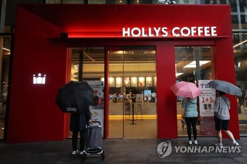 Pedestrians walk in front of a coffee shop in southern Seoul on Aug. 3, 2020, where at least 10 COVID-19 patients have been confirmed to have been infected. (Yonhap)