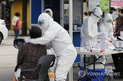In this photo, taken on Aug. 11, 2020, health workers give a citizen a COVID-19 test at a makeshift clinic near Namdaemun Market in Seoul after eight merchants there tested positive for the virus. (Yonhap)