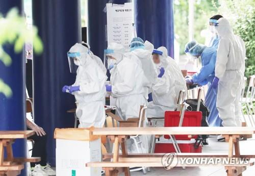 Health workers clad in protective gear prepare to work at a coronavirus screening clinic at a high school in Yongin, south of Seoul, on Aug. 13, 2020. (Yonhap)