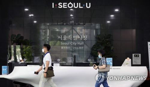 Officials leave Seoul City Hall on Aug. 19, 2020, as it was shuttered after a city official was confirmed to be infected with the novel coronavirus. (Yonhap)