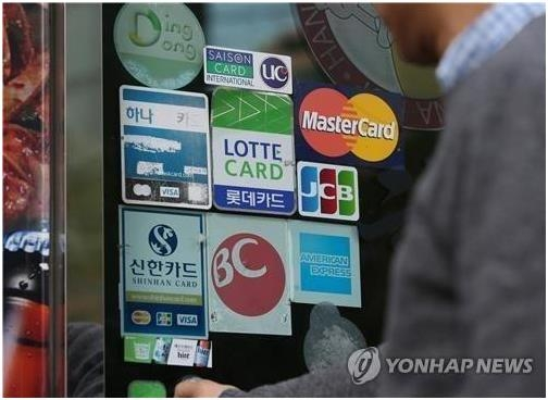 This undated file photo shows corporate logos of credit card companies in front of a store. (Yonhap)
