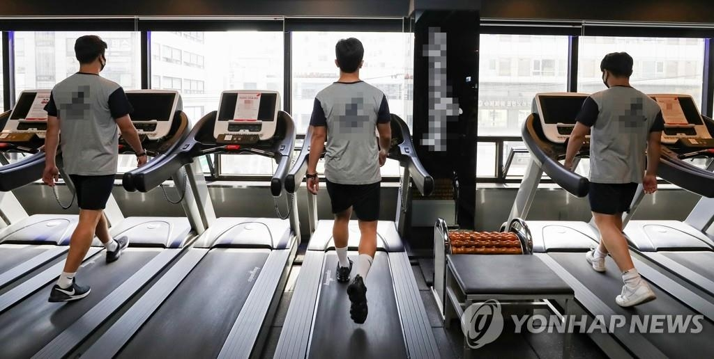 The undated file photo shows people, wearing masks, walking on treadmills. (Yonhap)