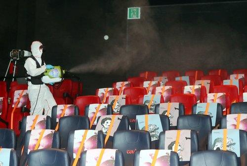 This file photo, taken on July 14, 2020, shows a worker disinfecting a CGV theater in Bucheon, just west of Seoul, to prevent spread of the new coronavirus. (Yonhap)