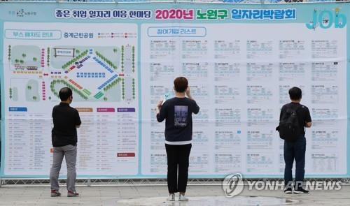 The file photo taken July 15, 2020, shows jobseekers looking at the floor plan of a recruitment event in Seoul. (Yonhap)