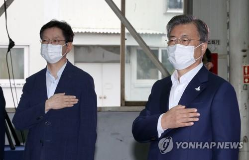 South Gyeongsang Province Gov. Kim Kyoung-soo (L) and President Moon Jae-in pledge allegiance to the national flag in an industrial event in Changwon, South Gyeongsang Province, on Sept. 17, 2020. (Yonhap)