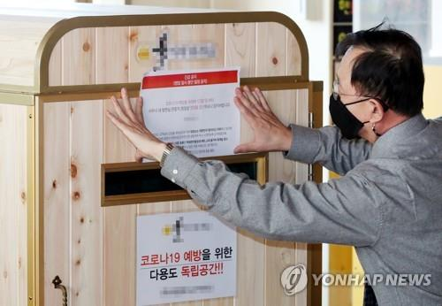 An official puts up a notice banning the use of sauna facilities at a public bath in Incheon, west of Seoul, on Nov. 30, 2020, as the central government toughened social distancing rules until Dec. 7 amid the resurgence of the coronavirus. (Yonhap)