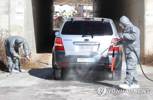 Quarantine officials disinfect a car on a road in Gumi, North Gyeongsang Province, southeastern South Korea, on Dec. 16, 2020, after an outbreak of highly pathogenic avian influenza was confirmed at a nearby chicken farm. (Yonhap)
