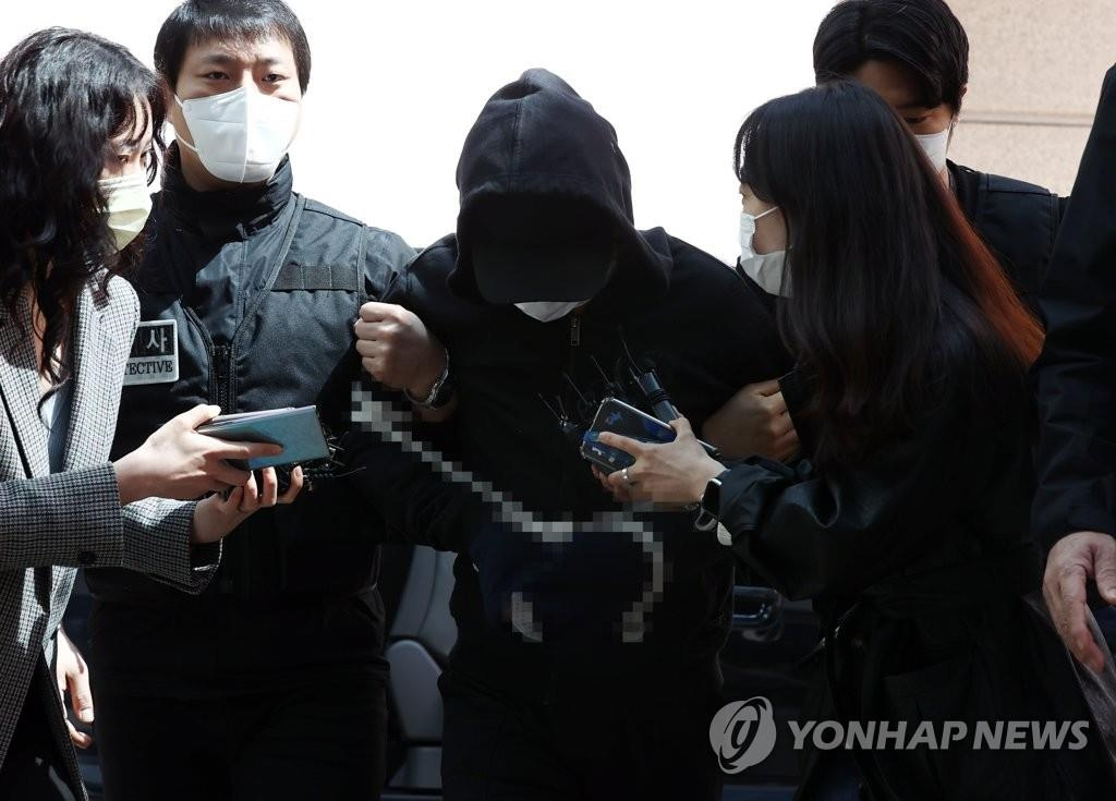 Kim Tae-hyun, the suspect in an alleged stalking murder case, is being escorted to attend a trial for his arrest warrant at the Seoul Northern District Court on April 4, 2021. (Yonhap)
