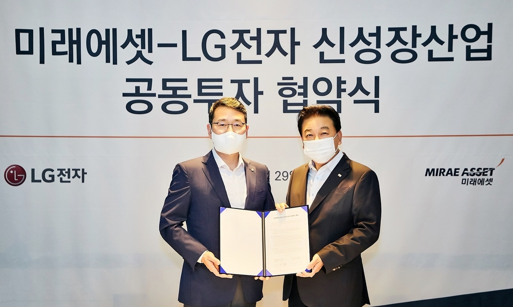 This photo provided by LG Electronics Inc. on April 30, 2021, shows Cho Joo-wan (L), the chief strategy officer of LG Electronics, and Lee Man-hee, head of Mirae Asset Capital Co., posing for a photo after signing an agreement to establish a venture capital fund in Seoul. (PHOTO NOT FOR SALE) (Yonhap)
