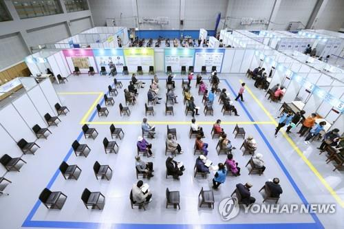 People wait for COVID-19 vaccine shots at an injection center in central Seoul, in the file photo taken May 3, 2021. (Yonhap)