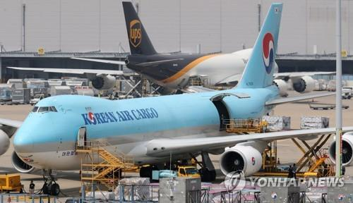 Workers unload boxes carrying 1.6 million doses of Pfizer Inc.'s COVID-19 vaccine, which the government has secured under a direct contract with the pharmaceutical giant, from a chartered plane at Incheon International Airport, west of Seoul, on Aug. 11, 2021. (Yonhap)