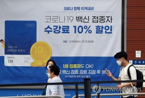 A banner informing of a 10 percent off tuition fee for vaccinated people is put up at a private educational institute in western Seoul on Sept. 28, 2021. (Yonhap)