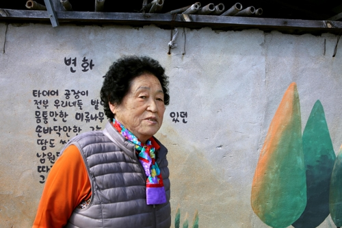 마을에서 만난 김점순 할머니. 본인이 쓴 시를 배경으로 포즈를 취해 주셨다. [사진/권혁창 기자]