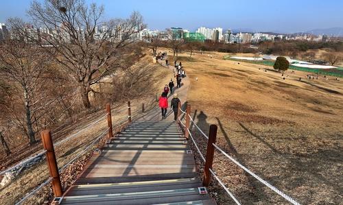 몽촌토성 위로 사람들이 걷고 있다. 토성 보존을 위해 산책로를 성 아래쪽으로 옮겨야 한다는 지적이 많다. 오른쪽 윗부분은 발굴 작업이 진행 중인 곳이다.[사진/조보희 기자]