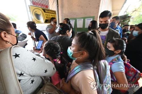 개학 첫날인 지난 16일 미 LA의 그랜트 초등학교에 마스크를 쓴 학생과 학부모가 도착해 들어가려 하고 있다. [AFP=연합뉴스]