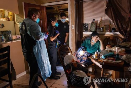 25일(현지시간) 미 텍사스주 휴스턴소방서의 구급요원들이 코로나19 증세를 보이는 여성을 병원으로 이송할 준비를 하고 있다. [AFP=연합뉴스]