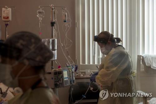 지난달 27일 미 캘리포니아 소노라의 어드밴티스트 헬스 병원 중환자실에서 한 간호사가 코로나19 환자의 상태를 살펴보고 있다. [AFP=연합뉴스]