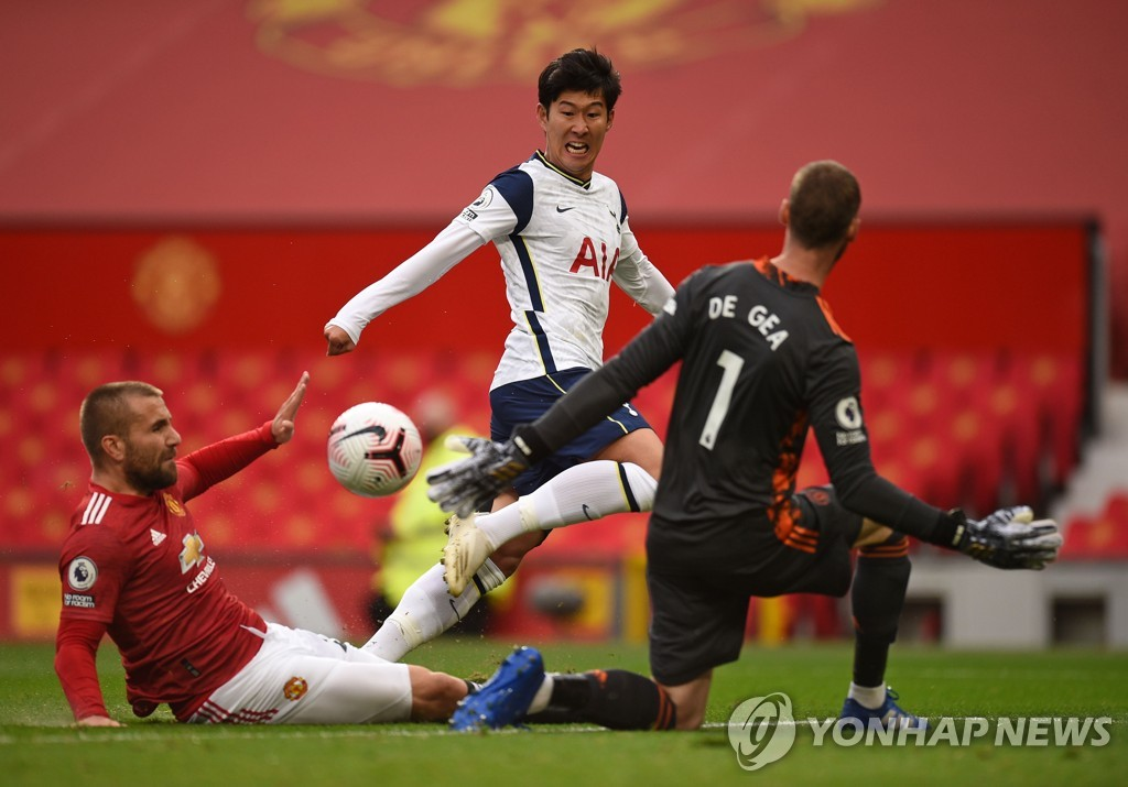 In this AFP file photo from Oct. 4, 2020, Son Heung-min of Tottenham Hotspur (C) scores past Manchester United goalkeeper David de Gea (R) during the clubs' Premier League match at Old Trafford in Manchester, England, 2020. (Yonhap)