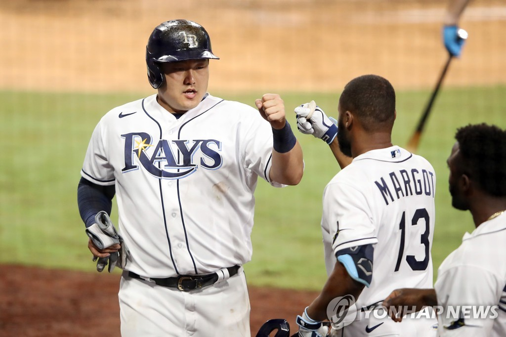 In this Getty Images photo, Choi Ji-man of the Tampa Bay Rays (L) celebrates with teammate Manuel Margot after scoring on a Mike Zunino sacrifice fly against the Houston Astros during the bottom of the sixth inning of Game 7 of the American League Championship Series at Petco Park in San Diego on Oct. 17, 2020. (Yonhap)