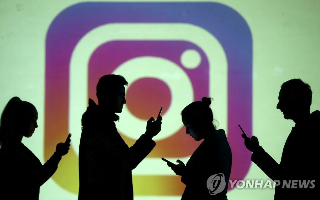 인스타그램 로고를 배경으로 촬영된 모바일 이용자들의 실루엣