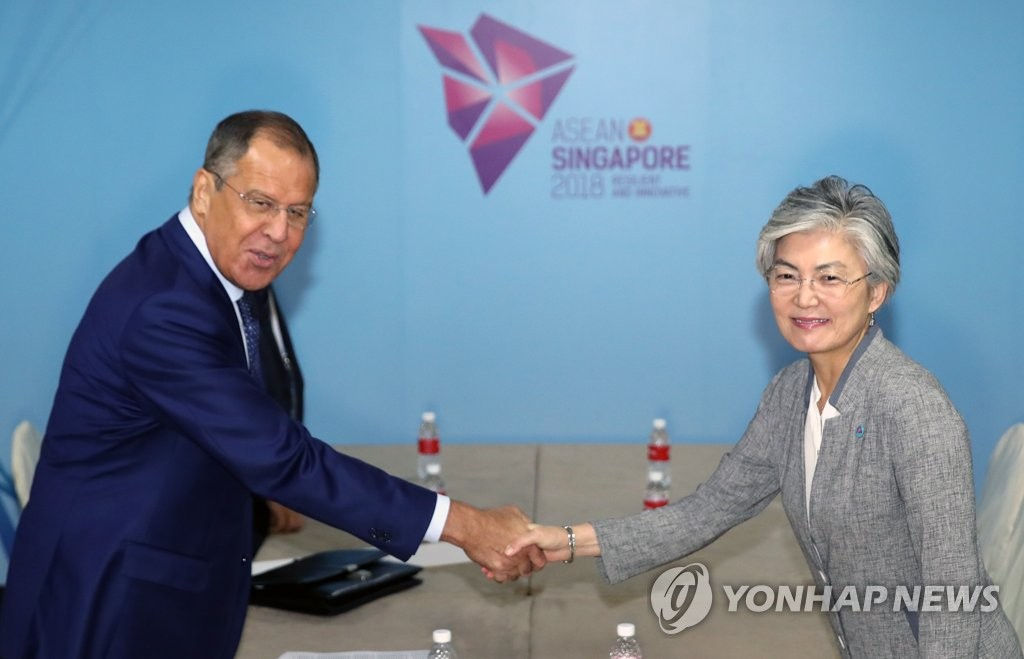 This photo, taken on Aug. 2, 2018, shows South Korean Foreign Minister Kang Kyung-wha (R) shaking hands with her Russian counterpart, Sergey Lavrov, before their talks on the sidelines of the ASEAN Regional Forum in Singapore. (Yonhap)
