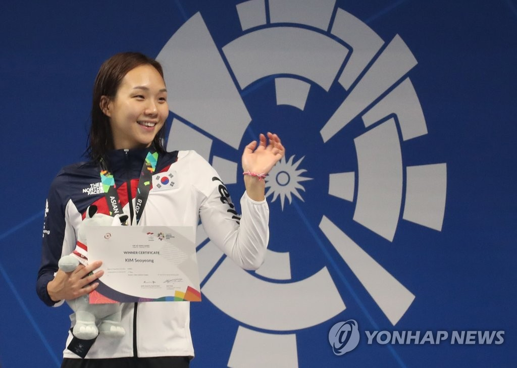 In this file photo from Aug. 24, 2018, South Korean swimmer Kim Seo-yeong waves to the crowd after winning the gold medal in the women's 200-meter individual medley at the 18th Asian Games at GBK Aquatic Center in Jakarta. (Yonhap)