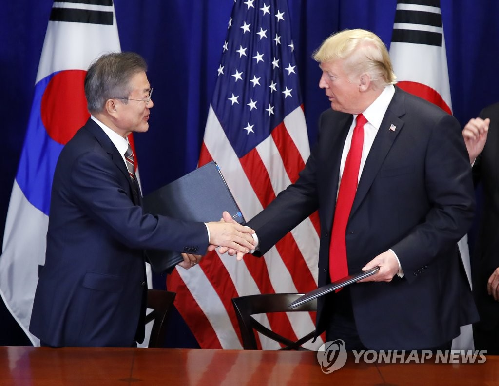 South Korean President Moon Jae-in (L) and U.S. President Donald Trump shake hands after signing the official document on the revised free trade agreement between the two allies at Lotte New York Palace in New York on Sept. 24, 2018. (Yonhap)