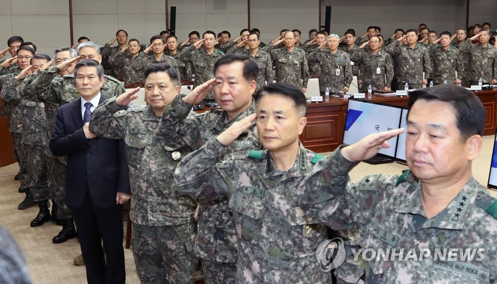 Defense Minister Jeong Kyeong-doo, clad in a black suit, and top commanders salute the national flag during a Seoul meeting on Dec. 5, 2018. (Yonhap)