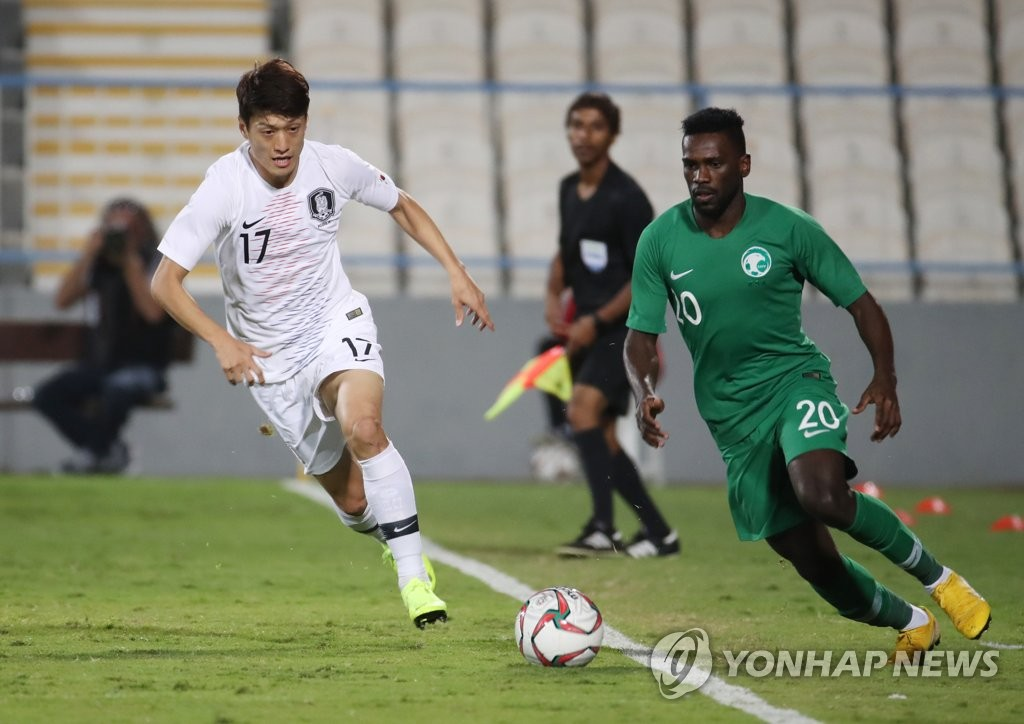 Lee Chung-yong of South Korea (L) and Abdulaziz Al-Bishi of Saudi Arabia battle for the ball during their football friendly match at Baniyas Stadium in Abu Dhabi on Dec. 31, 2018. (Yonhap)