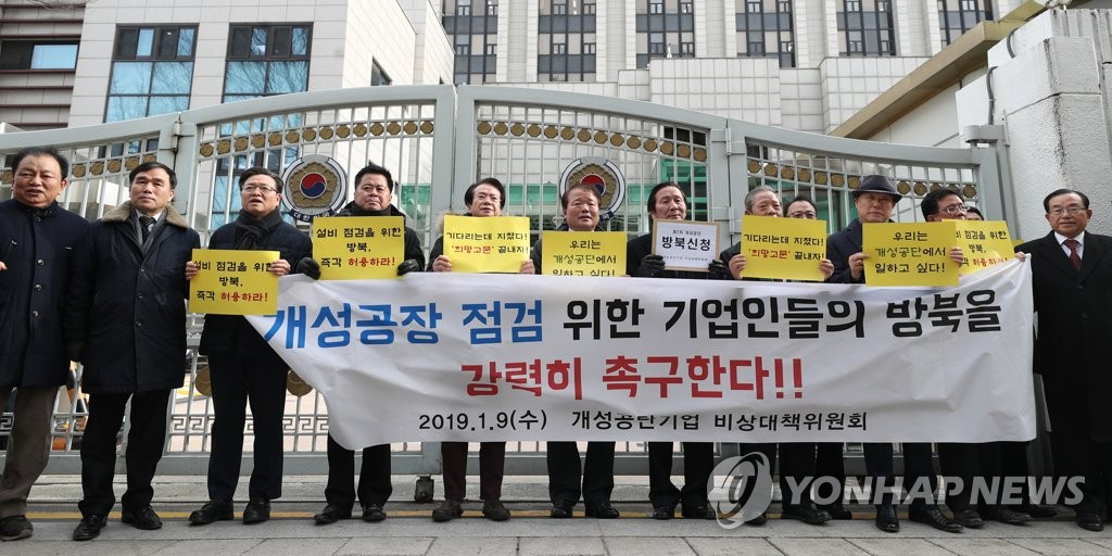 A group of businesspeople who once operated plants in the Kaesong Industrial Complex stands in front of a government building in central Seoul on Jan. 9, 2019, with a placard calling for state approval for a trip to the North Korean border town to check assets they left behind. (Yonhap)