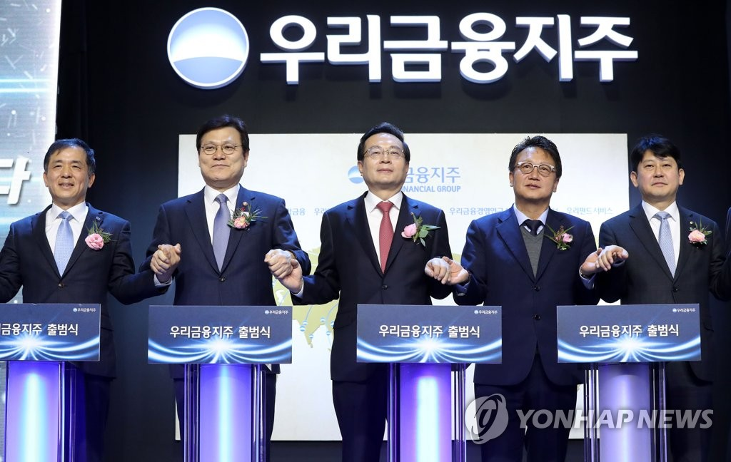 Sohn Tae-seung (C), CEO of Woori Financial Co., poses for a picture with officials that include Choi Jong-ku (2nd from L), chairman of the Financial Services Commission, during a ceremony marking the launch of the financial group in Seoul on Jan. 14, 2019. (Yonhap)