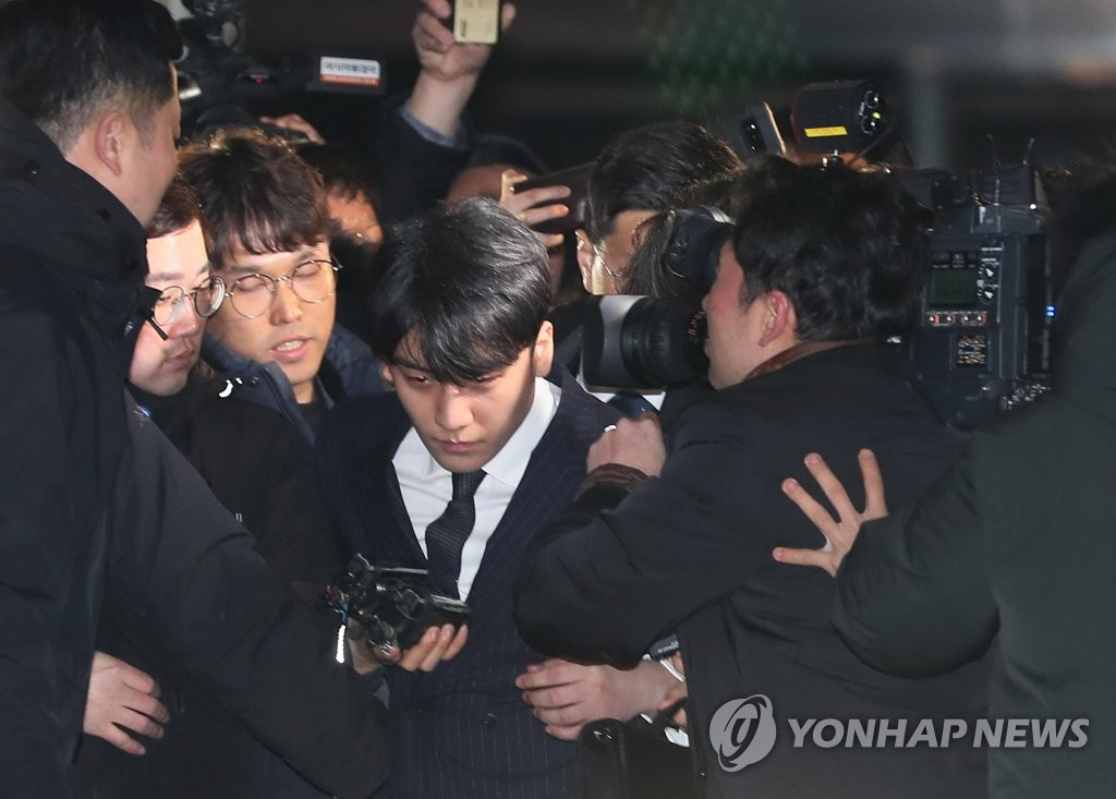 BIGBANG's Seungri pushes through a swarm of reporters at the Seoul Metropolitan Police Agency on March 15, 2019, after being grilled by police for 16 hours over alleged sex tapes and illegal activities at a nightclub. (Yonhap)