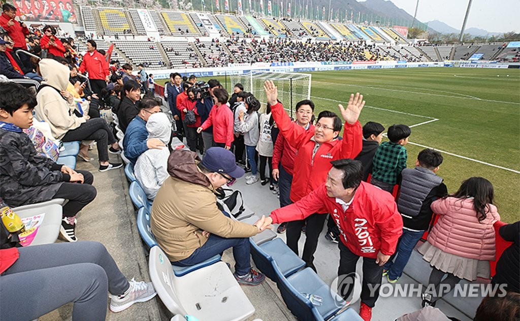 In this photo posted on the Liberty Korea Party's website, LKP chairman Hwang Kyo-ahn (2nd from R) raises his hands, while the party's by-election candidate, Kang Ki-youn, shakes hands with a football fan at Changwon Football Center in Changwon, some 400 kilometers south of Seoul, on March 30, 2019, ahead of the K League 1 match between Gyeongnam FC and Daegu FC. (Yonhap)
