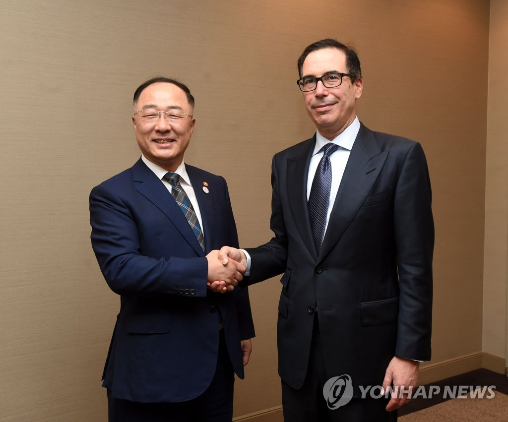 Hong Nam-ki (L), the minister of economy and finance, shakes hands with U.S. Treasury Secretary Steven Mnuchin at a hotel on the sidelines of an annual meeting of the Group of 20 finance ministers in Japan on June 9, 2019, in this photo provided by the ministry. (PHOTO NOT FOR SALE) (Yonhap)