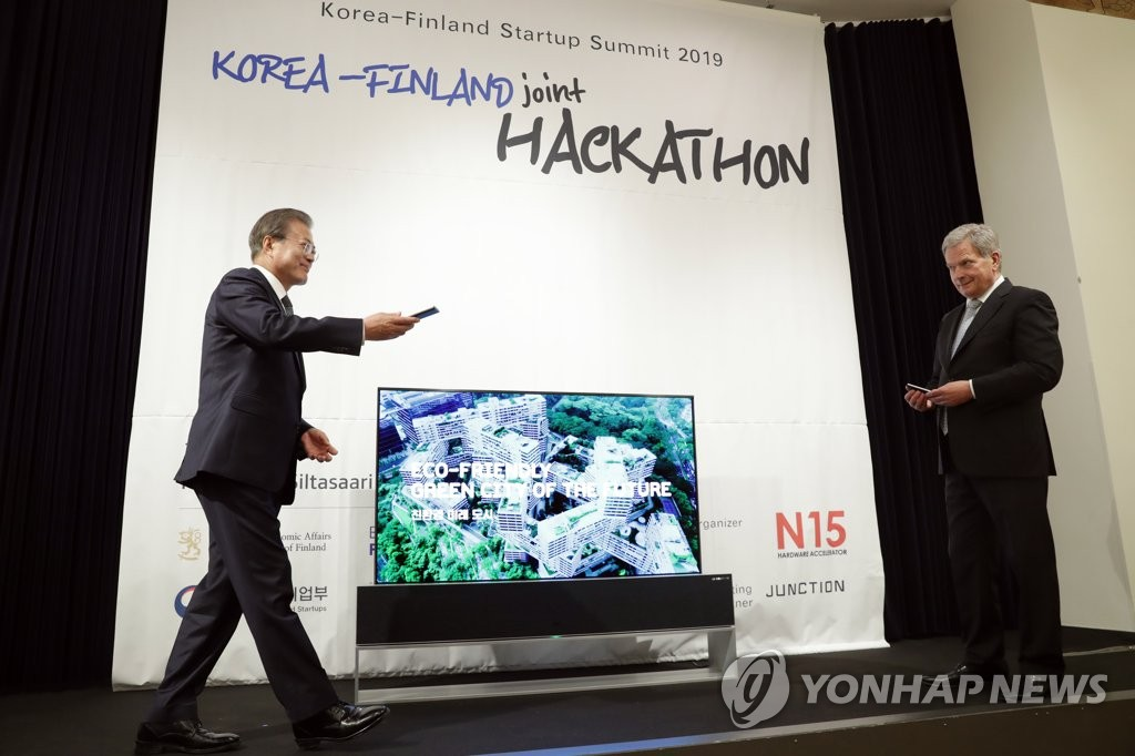 South Korean President Moon Jae-in (L) and Finnish President Sauli Niinisto unveil a mission for participants in the Hackathon contest, a program of the bilateral Startup Summit, in Helsinki on June 11, 2019. (Yonhap)