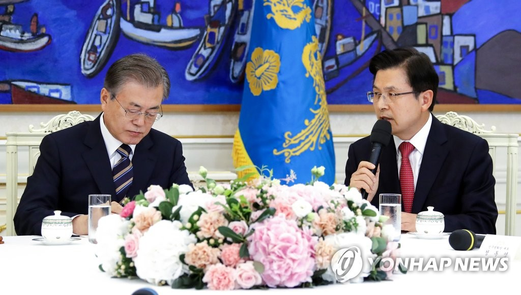 President Moon Jae-in (L) takes notes as Hwang Kyo-ahn, head of the conservative main opposition Liberty Korea Party, speaks at a Cheong Wa Dae meeting in Seoul on July 18, 2019. (Yonhap)