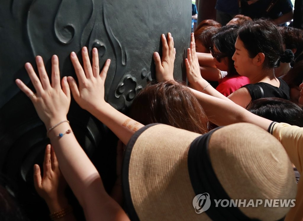 Parents of students who are seniors in high school touch the bell at Bosingak in central Seoul on Aug. 6, 2019, 100 days ahead of this year's college entrance exam, praying for their children. (Yonhap)