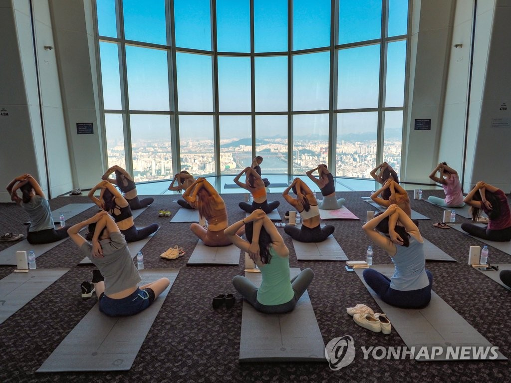 This photo taken on Aug. 14, 2019 and provided by Lotte World Tower & Lotte World Mall shows women in leggings participating in a yoga class at the country's tallest building in eastern Seoul. (PHOTO NOT FOR SALE)(Yonhap)