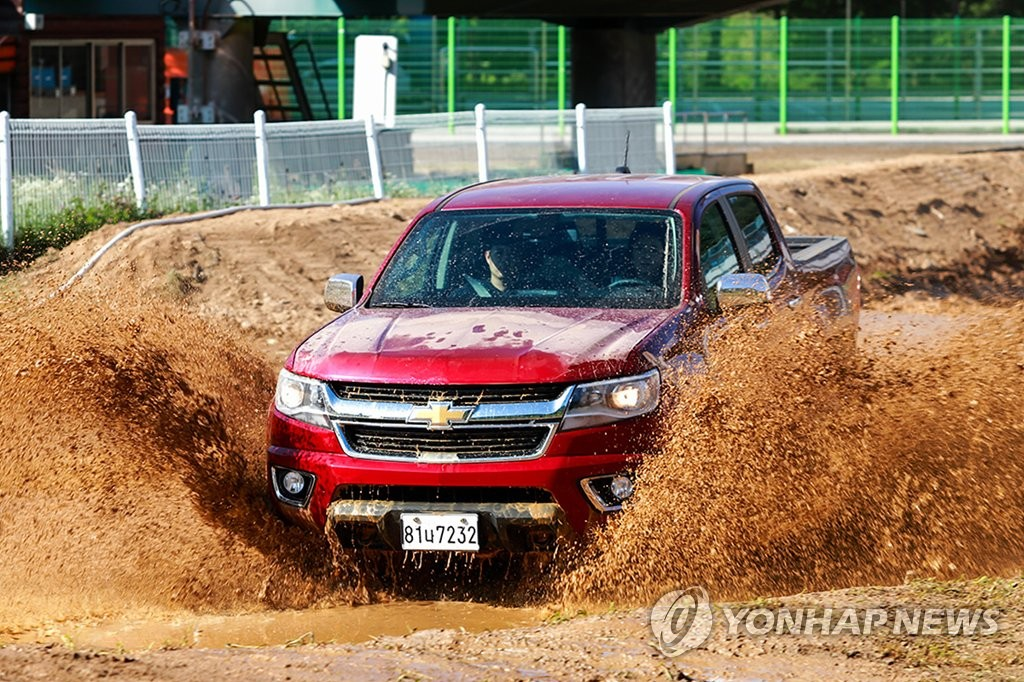 In this photo taken on Aug. 26, 2019, a Chevrolet Colorado pickup truck drives through an 80 centimeter-deep waterway during a media launching event held in Hoengseong, Gangwon Province. (Yonhap)