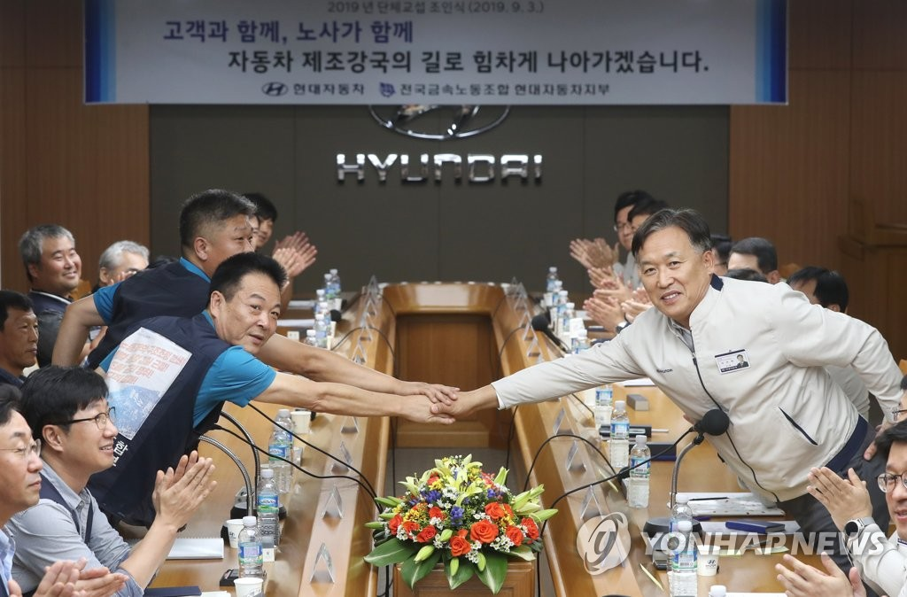 Representatives from Hyundai Motor Co.'s management and labor union shake hands after signing a collective bargaining agreement at the company's plant in Ulsan on Sept. 3, 2019. (Yonhap)