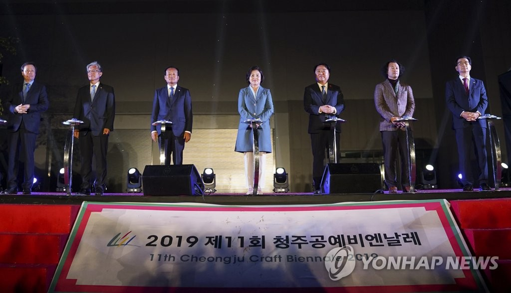 First lady Kim Jung-sook (C), Cheongju Mayor Han Beum-deuk (3rd from R) and other dignitaries push buttons to declare the start of the Cheongju Craft Biennale at the opening ceremony in the central city of Cheongju on Oct. 7, 2019. Han is the chief of the organizing committee. (Yonhap)