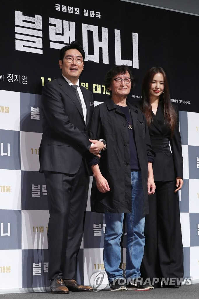 "Chung Ji-young (C), director of ""Black Money,"" flanked by the film's two main actors, poses for photos at a news conference to promote his white-collar crime film at a CGV theater in southern Seoul on Oct. 10, 2019. (Yonhap)"