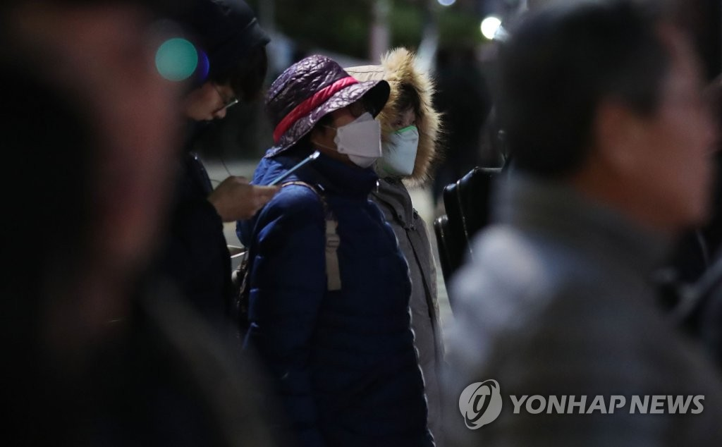 People wearing masks and thick jackets wait to cross the street during the evening rush hour in central Seoul on Nov. 18, 2019. (Yonhap)