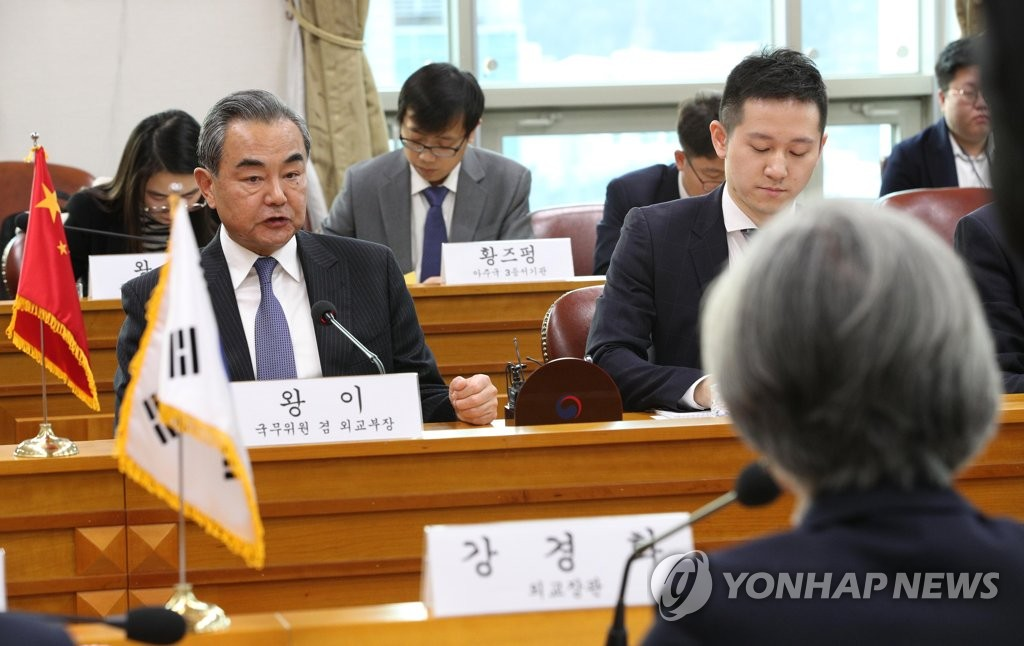 Chinese Foreign Minister Wang Yi (L) speaks at a meeting with his South Korean counterpart, Kang Kyung-wha (R, facing away), in Seoul on Dec. 4, 2019. (Yonhap)